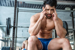 Pensive man sitting on the bench gym Royalty Free Stock Photography