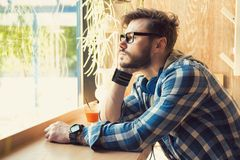 Pensive man sitting in cafeteria royalty free stock photography