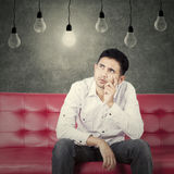 Pensive man sitting on couch and look at lamp Stock Photos