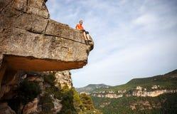 Pensive man sitting on edge of cliff Royalty Free Stock Photos