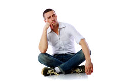 Pensive man sitting at the floor Stock Photos