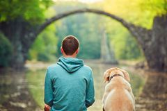 Pensive man sitting with his dog. Pensive young man sitting on the pond bank with a his dog - Amazing place in Germany. Rakotzbrucke also known as Devils Bridge Stock Photography