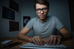 Pensive man sitting at home and typing on keyboard Stock Photography