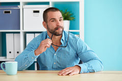 Pensive man sitting in the office stock photos
