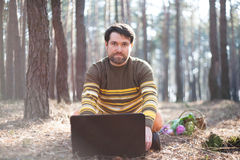Pensive man sitting outdoors using a laptop computer. A pensive man sitting outdoors in the sunny forest using a laptop computer Royalty Free Stock Photo