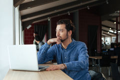 Pensive man sitting at the table with laptop Royalty Free Stock Photos