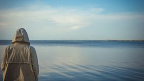 The pensive man standing near the sea stock photo