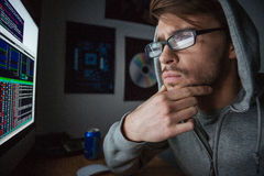 Pensive man in sweatshirt with hood thinking and coding Royalty Free Stock Images