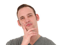 Pensive man thinking. Pensive attractive young man standing thinking with his hand to his chin and a faraway look in his eyes isolated on white Royalty Free Stock Photography