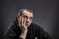 Pensive man thinking. Pensive man with palm on his cheek thinks over gray Royalty Free Stock Photography
