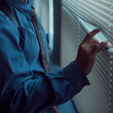 Pensive man thinking of something behind venetian blind, makes the gap. Pensive man thinking of something behind venetian blind Royalty Free Stock Photo