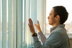 Pensive man thinking of something behind venetian blind. The young guy pushes the vertical blinds in front of window and looking into the distance. Businessman Stock Photos