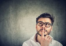 Pensive man trying to make decision. Young handsome man in glasses thinking in doubts and touching lips on gray Royalty Free Stock Photos
