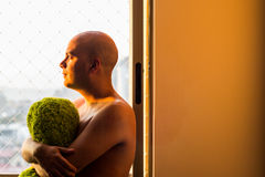 Pensive man at the window. In sunset Stock Photo