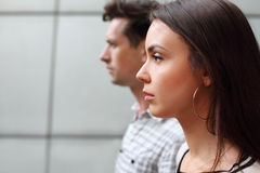 Pensive man and woman stand near wall Royalty Free Stock Images