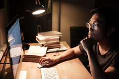 Pensive man working with computer and thinking in the evening Royalty Free Stock Photos