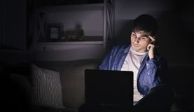 Pensive man working late at home on laptop stock photo