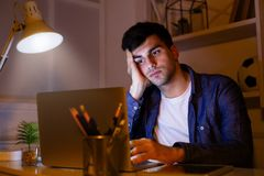 Pensive man working late at home office royalty free stock images