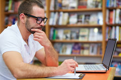Pensive man working in the library Royalty Free Stock Photos