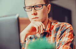 Pensive man working over the laptop Stock Image