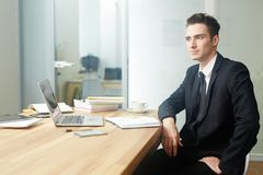 Pensive manager. Attractive businessman in suit sitting by desk in office and brainstorming royalty free stock photo