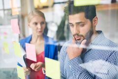 Troublesome point. Pensive manager looking at working note while his colleague offering the best solution Stock Image
