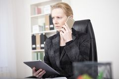 Pensive Manageress with Tablet Calling on Phone. Close up Pensive Manageress in Black Business Attire Holding a Tablet Device While Calling to Someone Using Stock Images