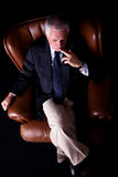 Pensive mature businessman seated on a chair Royalty Free Stock Photography
