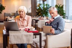 Pensive mature couple immersing in digitalization. Gadget for everyone. Thoughtful nice mature couple sitting on chairs and looking at screens while using tablet Royalty Free Stock Photography