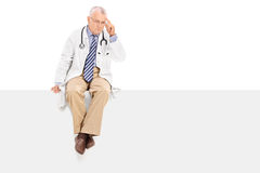 Pensive mature doctor sitting on a blank panel Stock Image