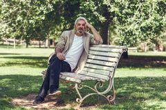 Pensive mature man sitting on bench in an urban park. Stock Image