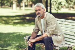 Pensive mature man sitting on bench in an urban park. Portrait of a pensive mature man sitting on a bench in an urban park. Senior male with white hair and Royalty Free Stock Image