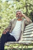 Pensive mature man sitting on bench in an urban park. Stock Photography