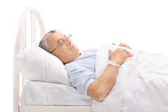 Pensive mature patient laying on bed royalty free stock images