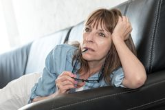 Pensive mature woman lying on sofa. At home Royalty Free Stock Image