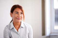 Pensive mature woman smiling and thinking Stock Photo