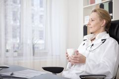 Pensive Medical Doctor with Drink Sitting on Chair Royalty Free Stock Images
