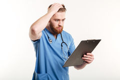 Pensive medical doctor or nurse with stethoscope looking at clipboard. Portrait of a pensive medical doctor or nurse with stethoscope looking at clipboard Stock Photos