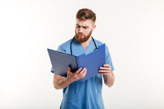Pensive medical doctor or nurse with stethoscope looking at clipboard. Portrait of a pensive medical doctor or nurse with stethoscope looking at clipboard Stock Image