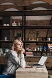 Pensive middle aged woman holding credit card and looking away while using laptop with website. On screen royalty free stock images