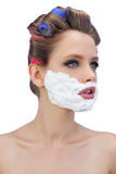 Pensive model in hair curlers with shaving foam Stock Image