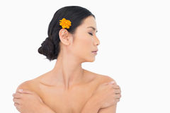 Pensive model with orange flower in hair touching her shoulders Royalty Free Stock Images