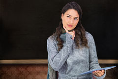Pensive model wearing winter clothes holding her tablet Royalty Free Stock Photos