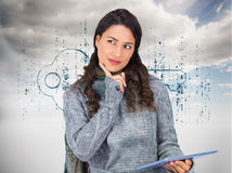 Pensive model wearing winter clothes holding her tablet Stock Photography