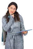 Pensive model wearing winter clothes holding her tablet Royalty Free Stock Images