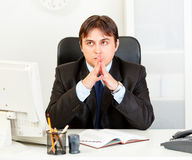 Pensive modern business man sitting at desk Royalty Free Stock Images