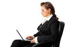 Pensive modern business woman using laptop stock photo