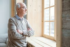 Medicative senior man staring through window. Pensive mood. Thoughtful attractive senior man gazing through window while crossing hands and staying Stock Image