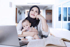 Pensive mother with baby and laptop Stock Images