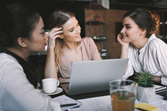 Pensive multicultural businesswomen working and discussing project in cafe. Smiling pensive multicultural businesswomen working and discussing project in cafe royalty free stock image